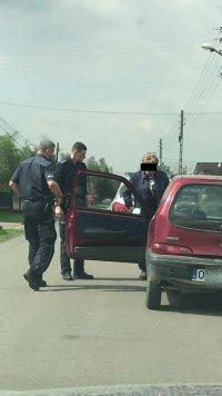 Po prawej samochód marki Fiat Seicento, po lewej dwaj policjanci kontrolują starszego mężczyznę w peruce.